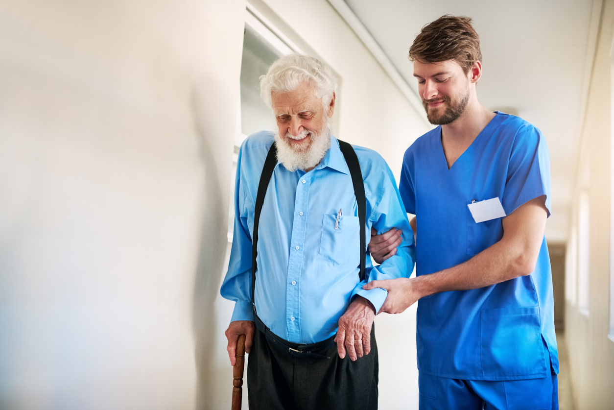 Male Carer with Elderly man with a walking stick walking down a coridor
