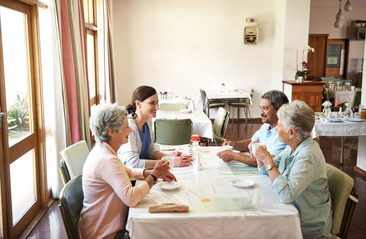 carer-with-elderly-people-by-the-table