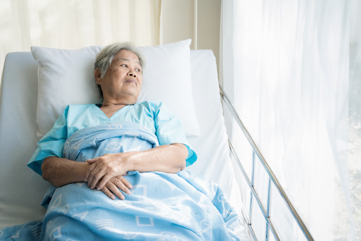 elderly asian woman in hospital bed