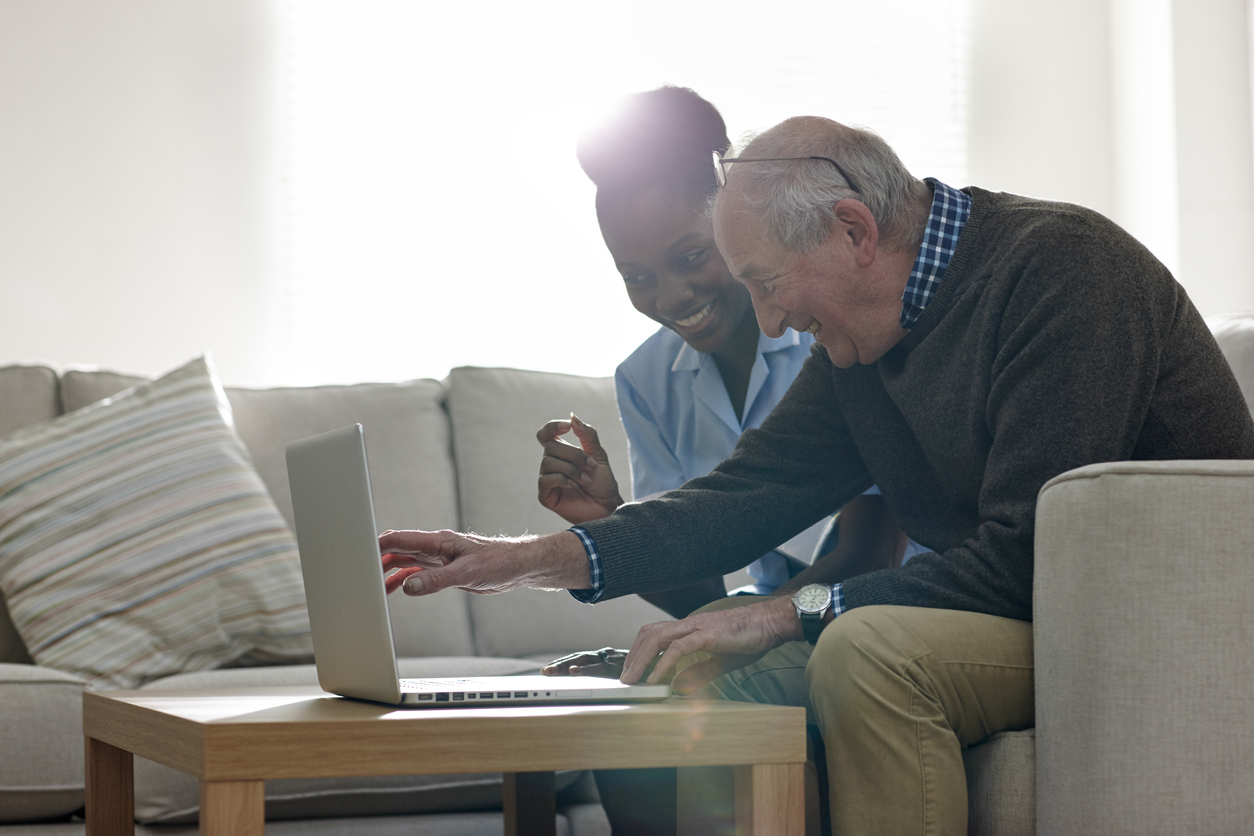 nurse and elderly person with laptop